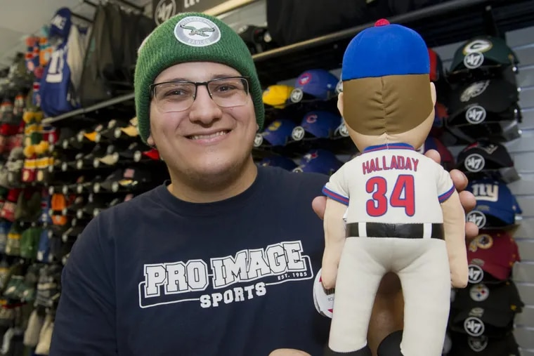 """Pro Image Sports sales associate Mike Sisto holds a Roy Halladay """"Plush Player"""" doll in the Gloucester Premium Outlets store.  Pro Image began a promo on Nov. 11, where 100 percent of the profits from any Roy Halladay merchandise will be donated to the Roy Halladay Family Foundation through the end of 2017."""