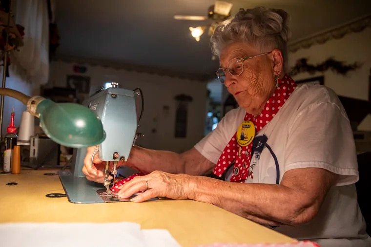 Mae Krier, 95, of Levittown, Bucks County, an original Rosie the Riveter, shows how she made thousands of pandemic masks based on the red-with-white-polka-dot design of the iconic Rosie bandanna.