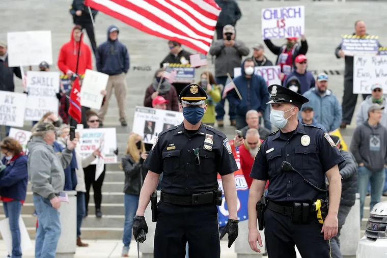 Police direct traffic as protesters gather Monday outside the Pa. capitol in Harrisburg Monday. No citations were issued to protesters who broke the state's stay-at-home order, Capitol Police said.
