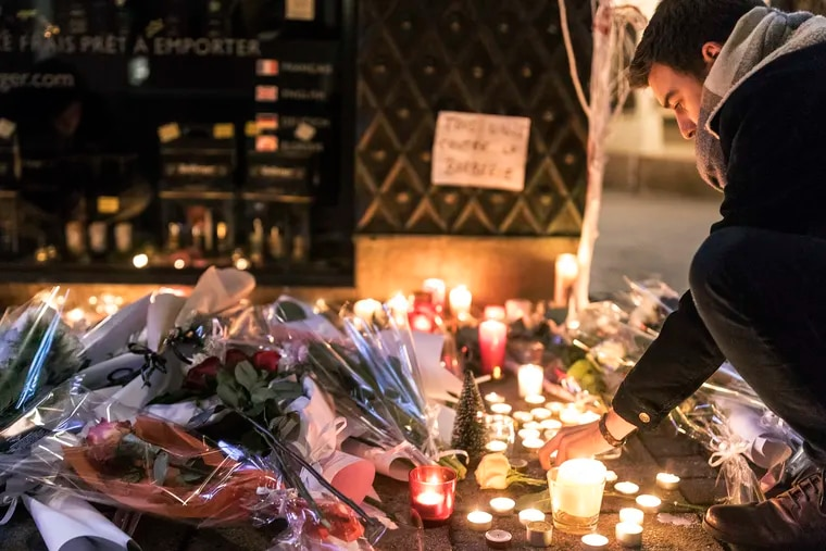 """A man lights a candle as he pays respects to the victims the night following an attack that killed three persons and wounding at least 13, in Strasbourg, eastern France, Wednesday, Dec. 12, 2018. More than 24 hours after a man sprayed gunfire at crowds in France's largest Christmas market as he shouted """"God is great!"""" over 700 security forces combed the eastern city of Strasbourg on Wednesday for the 29-year-old suspect who's been in trouble with the law since age 10. (AP Photo/Jean Francois Badias)"""