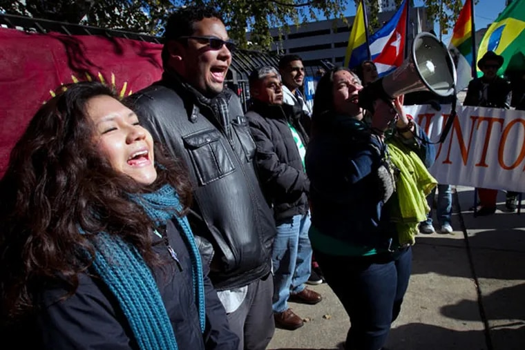 Juntos members (from left) Olivia Vasquez, Miguel Andrade and Erika Almiron during a rally outside immigration offices at North 16th and Callowhill streets on Friday, November 21, 2014.