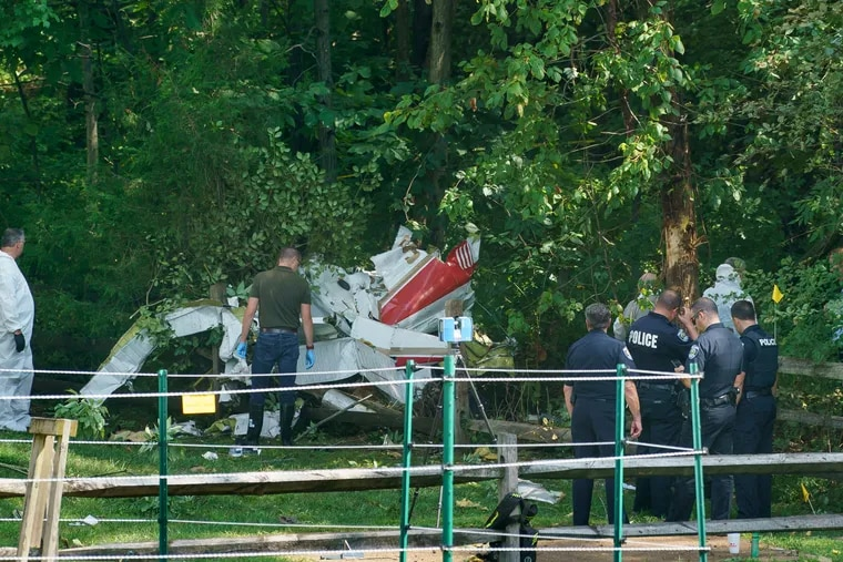 Officials investigate the scene of a small plane crash in a residential neighborhood in Upper Moreland.