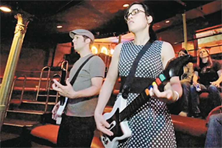 Rachel White takes on boyfriend Brian Rebuck in a Guitar Hero match at the Trocadero balcony. Nightclubs have begun to attract patrons who want to take their video-game fantasies public. (Ed Hille/Inquirer)