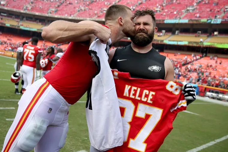Chiefs' tight end Travis Kelce plants a kiss on his brother, Eagles' center Jason Kelce (right), as they exchange jerseys after their game on Sept. 17, 2017. Sunday's matchup in South Philadelphia will be the first time the two teams, and brothers, face each other since.