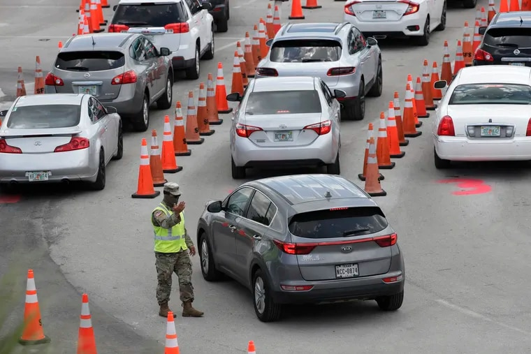 A National Guardsman directs traffic at a COVID-19 testing site outside Hard Rock Stadium in Miami Gardens, Fla.