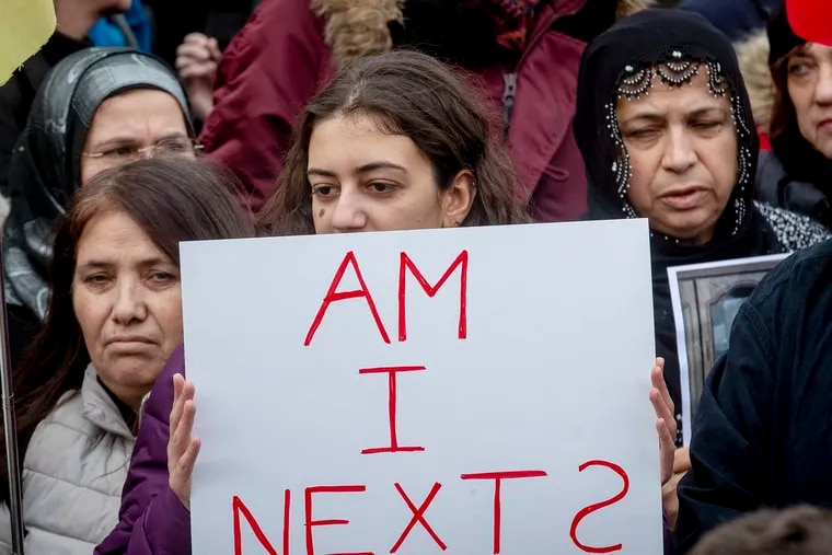 A woman holds up a poster during a solidarity rally in Hanau, Germany on Saturday, three days after several people were killed in a shooting at the city.