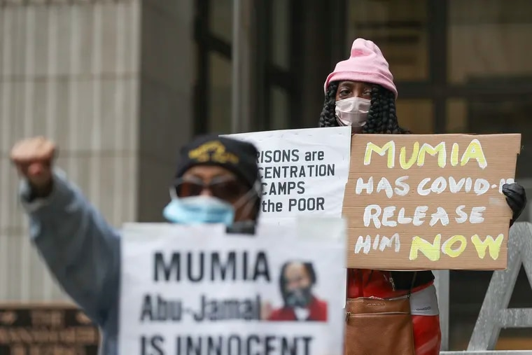 Cheryl Wright holds up a sign while in front, Pam Africa raises a fist as supporters of Mumia Abu-Jamal rally in front of the District Attorney's Office in Philadelphia on Saturday. Africa said they found out Friday that Abu-Jamal has COVID-19. Prison officials won't comment.