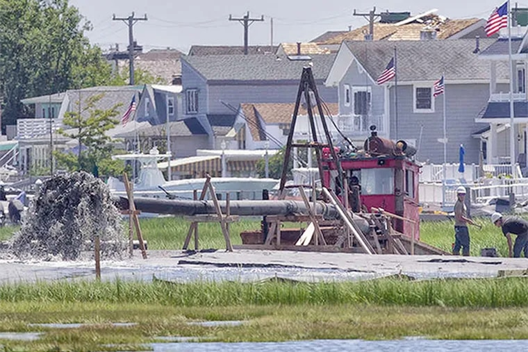 At a Stone Harbor salt marsh, engineers work on a restoration plan that involves spraying sand and muck over marshes.