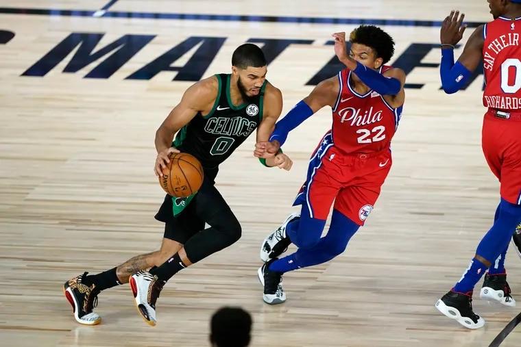 The Celtics' Jayson Tatum (0) drives toward the basket as the 76ers' Matisse Thybulle (22) defends.