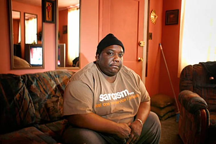 """Camden police accused Ron Mills of running away from a raid. Mills says he walks with a cane and weighed 325 pounds at the time. """"I'm so quick, I ran away,"""" he said sarcastically. (ED HILLE / Staff Photographer)"""