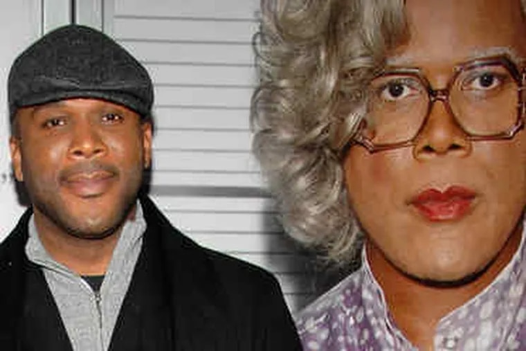 Tyler Perry with a poster of his character Madea, who he has said is based on his mother, Willie Maxine Perry, and an aunt.