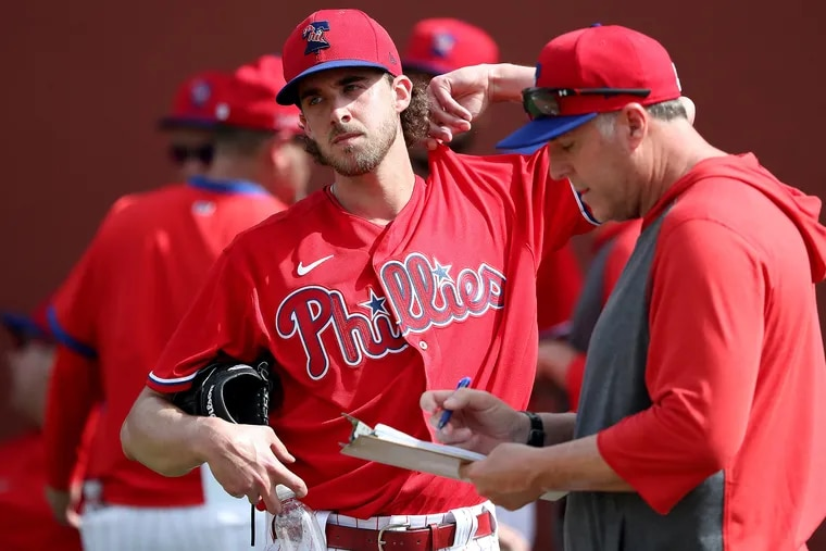 Phillies ace Aaron Nola talks with pitching coach Bryan Price, right, after throwing a bullpen session last week in Clearwater, Fla.