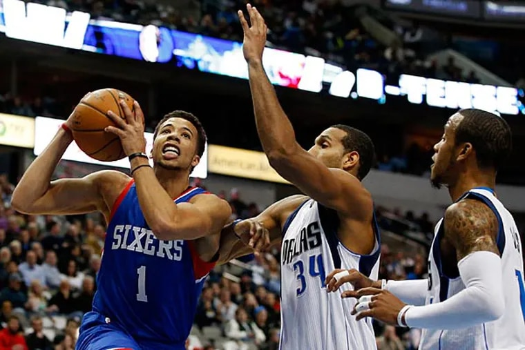 Philadelphia 76ers' Michael Carter-Williams (1) drives to the basket for a shot past Dallas Mavericks' Al-Farouq Aminu, from left, Brandan Wright (34) and Monta Ellis, right, in the first half of an NBA basketball game, Thursday, Nov. 13, 2014, in Dallas. (Tony Gutierrez/AP)