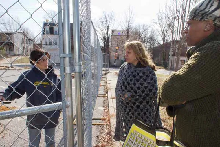 From behind a fence surrounding the Queen Lane Apartments, Rachael Fowler, CHRS, Inc. archeologist speaks with Lisa Hopkins of Northwest Neighbors of Germantown and (right) Kimberly J. Mathis, Habitat For Humanity board member.  Photo taken from the Priscilla St., side of the property, Philadelphia, March 13, 2013.  ( DAVID M WARREN / Staff Photographer )