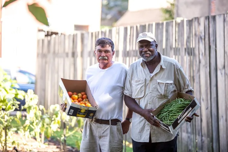 John Lindsay and James Seward stand with fresh produce from Wiota Street Community Garden, which was saved by the Philadelphia Redevelopment Authority last year.
