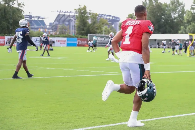 With Lincoln Financial Field in the background, Jalen Hurts runs onto the field before a joint workout with the New England Patriots on Aug. 17.
