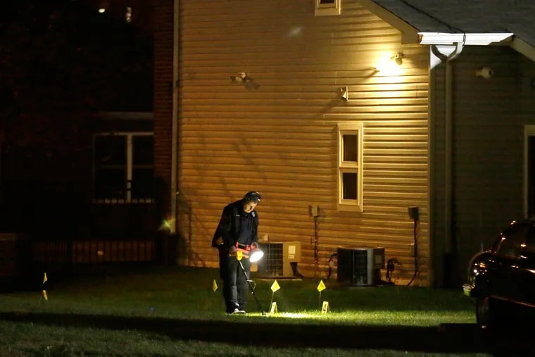 Philadelphia Police search for evidence behind homes after an off-duty policeman was shot on Friday, Nov. 18.