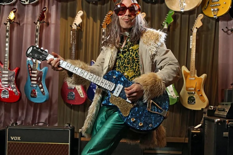 Chris DiPinto, all glammed up - check out the shoes - at his guitar shop in Fishtown. Creem Circus is not a tribute band, he says. He wrote all the songs on the album. ( Michael Bryant / Staff Photographer )