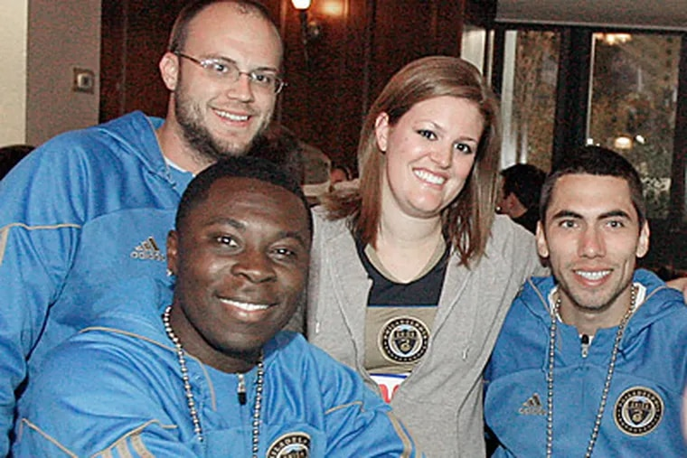 Matt Vlock and Michelle Stella (standing) pose with Union players Freddy Adu and Gabe Farfan. (Elizabeth Robertson/Staff Photographer)