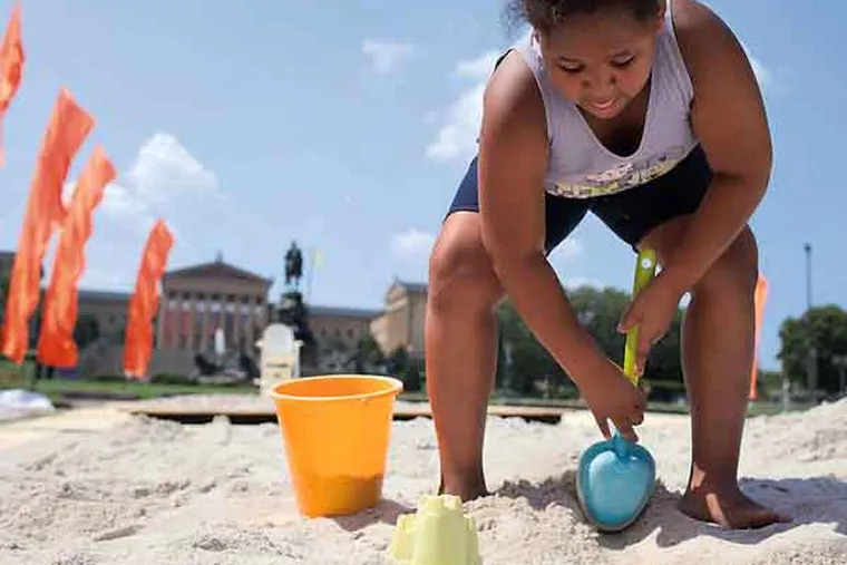 Peyton Moore, 8, from Philadelphia, gets some beach time at The Oval, a pop up park in Eakins Circle in Philadelphia on July 17, 2013.  ( ANDREW RENNEISEN / Staff Photographer )
