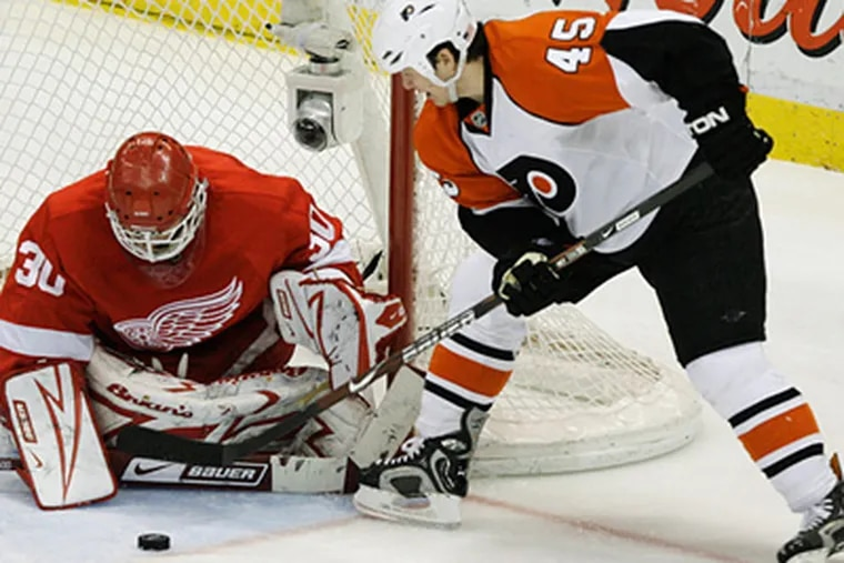 Detroit Red Wings goalie Chris Osgood stops a shot by Philadelphia Flyers' Arron Asham during the third period of an NHL hockey game in Detroit, Tuesday, March 17, 2009. Detroit won 3-2. (AP Photo/Paul Sancya)
