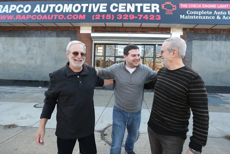 """Bruce Goldstein, left, Jason Goldstein, center, and Michael Goldstein, right, pose for a portrait outside their shop, Rapco Automotive Center, in Philadelphia, PA on November 21, 2019. They renovated the exterior of the shop. The work was part of the City of Philadelphia's program called the """"Storefront Improvement Program."""""""