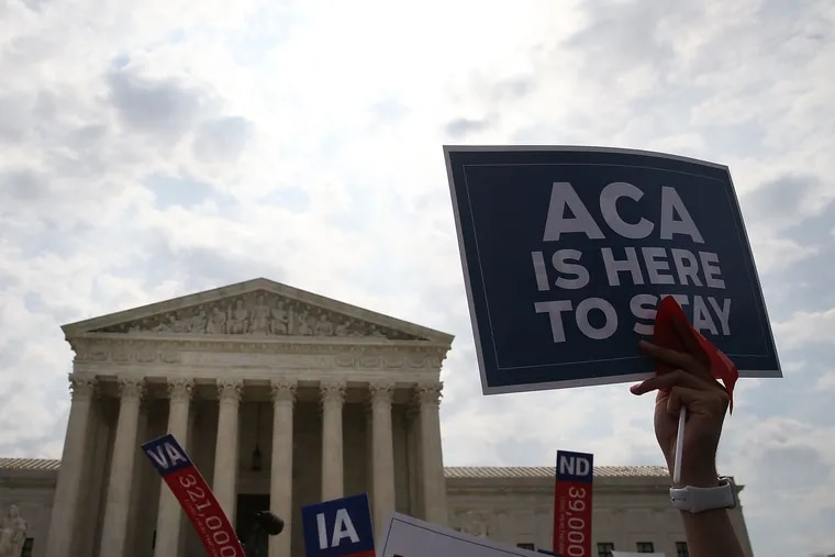 """In this file image of the U.S. Supreme Court building in 2016, a sign is held up that reads """"ACA Is Here To Stay"""" after a ruling was announced in favor of the Affordable Care Act. June 25, 2015, in Washington, D.C. Now down a justice since the passing of Ruth Bader Ginsburg, the Supreme Court will review a case challenging the ACA this fall."""