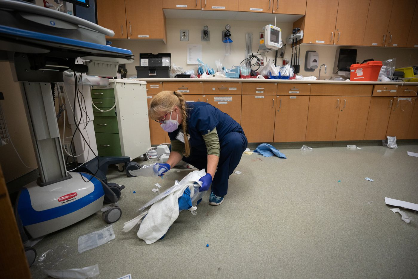 Cyndy Martinez, an ER nurse at Suburban Hospital, cleans up the floor inside the trauma room after the staff intubated and stabilized a critically ill patient. Martinez said she wanted to safely dispose of potential biohazards to help protect the hospital's cleaning staff.