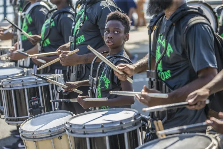 Terrell Hill, 11, center, of the Zodiac Percussion Drum Line, looks to one of the older drummers, as they make their way down Columbus Boulevard during a recent Labor Day Parade. MICHAEL BRYANT / Staff Photographer