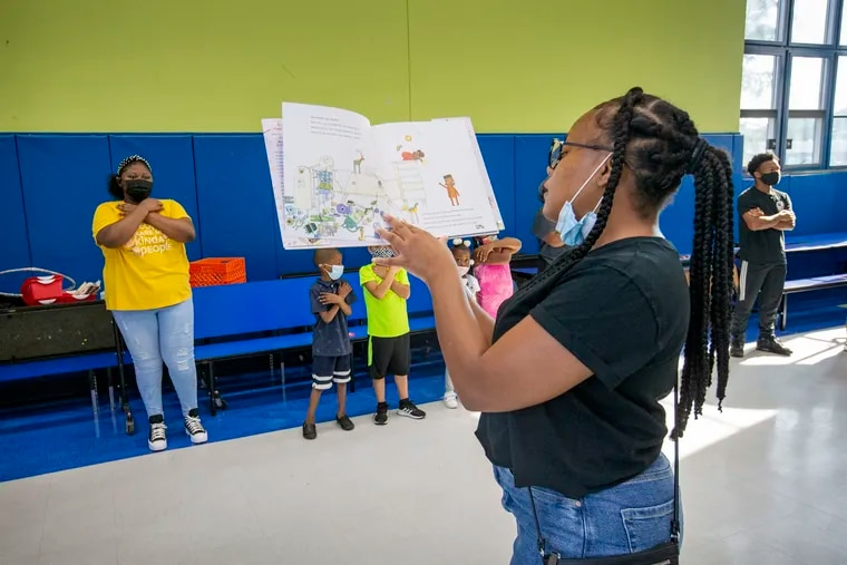 Bria Williams, lead coach at Freedom Schools Literacy Academy Harrity, reads Ada Twist Scientist by Andrea Beaty to students during Harambee circle.