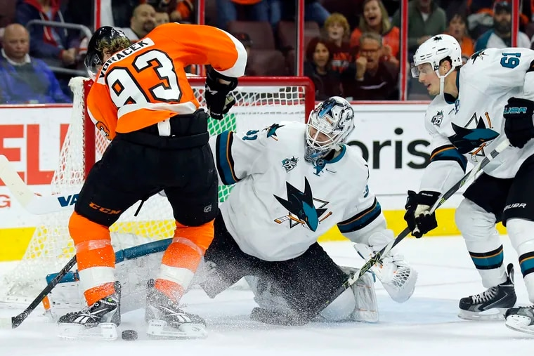 The Flyers' Jake Voracek (left) tries to score against San Jose Sharks goalie Martin Jones and Justin Braun in this file photo. Jones and Braun have been reunited with the Flyers.