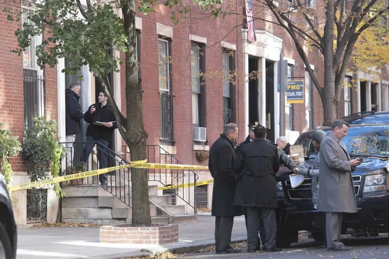 Investigators gather on the 1800 block of Pine Street, where a man was injured at 4 a.m. Tuesday opening a package that exploded.