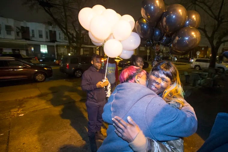 """A memorial event was held Friday at 47th and Brown Streets on the 18th anniversary of what has become known as the Lex Street Massacre. On Dec. 28, 2000, seven people were slain in the city's biggest mass killing on record. Here, Veronica Conyers, mother of victim Calvin """"CJ"""" Helton, is hugged on Dec. 28, 2018. The balloons were to be released later in the evening. CHARLES FOX / Staff Photographer"""