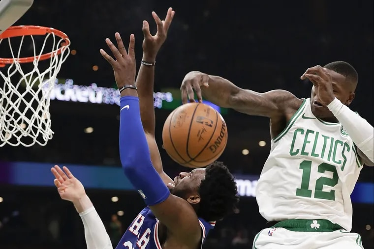Celtics guard Terry Rozier swats the shot of Sixers center Joel Embiid during the second quarter.
