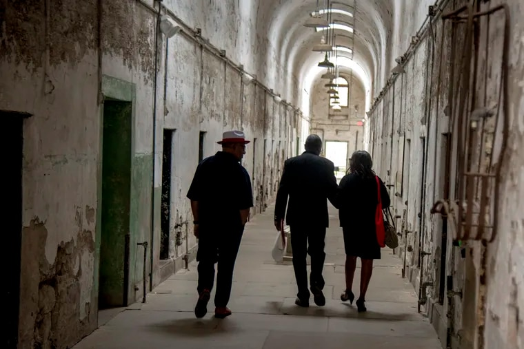 The last death row inmate at Eastern State Penitentiary, Samuel Barlow, and his fiancée, Karen Lee, tour an old cellblock as he returns to his old prison for the first time to receive an award from the Prison Society on Wednesday.