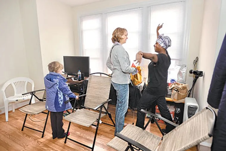 Imani Sullivan got a new job and an apartment after our readers helped her out. At Sullivan's housewarming party, Mariana Chilton, a child hunger expert at Drexel University's School of Public Health, is greeted by Sullivan's son, Asem, 4, and his friend Safee Jackson, 4. (Sharon Gekoski-Kimmel / Staff Photographer)