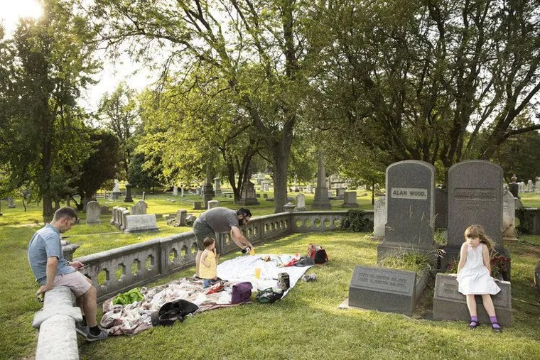 A family sets up for a picnic in the Woodlands cemetery in West Philly, which hosts a number of events to attract new visitors to its historic grounds.