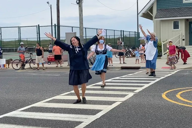 Barbara Wilson (front) dances with Joann Gahr and Doug Farrell as they perform 'The Sound of Music' with friends in a crosswalk in Longport, Atlantic County, on Saturday.