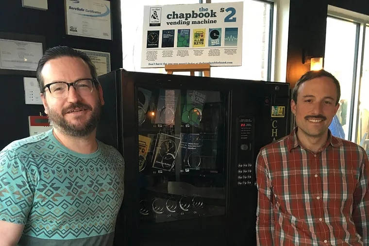 Ben Bigler (left) and Nic Esposito next to the chapbook vending machine at the Soup Kitchen Cafe in Fishtown.