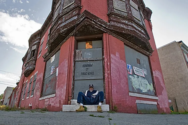A man who would not identify himself sits on the stoop of an abandoned building at the corner of Kaighn and Louis streets in Camden. (  David M Warren / Staff Photographer )