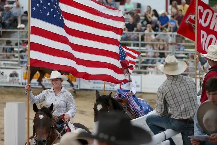 Katy Harris Griscom, left, carries the American flag during the grand entry on this year's opening night of the annual Cowtown Rodeo in Pilesgrove, N.J., on Saturday, May 26, 2018. Griscom and her husband, RJ, took over rodeo operations this year from her father. The weekly rodeo is now in its 64th consecutive year.