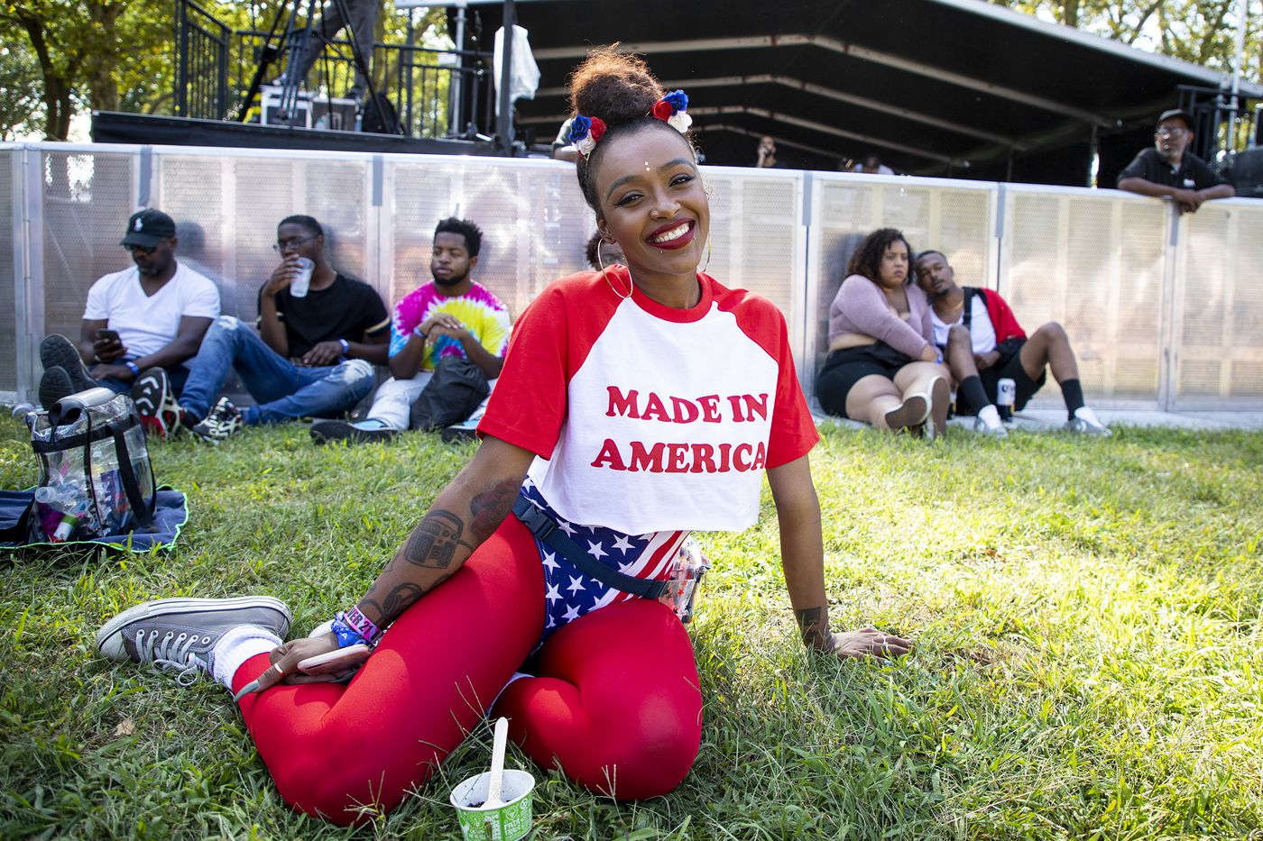 """Ronnae Beech, 28, of San Diego, Cali., came down to Made in America for her fourth year and is listening to Jorja Smith at the Liberty stage on the first day of the Made in America Festival on the Benjamin Franklin Parkway in Philadelphia on Saturday, Aug. 31, 2019. Beech is wearing a Made in America cropped t-shirt she found on Pretty Little Thing women's fashion clothing and a American Flag body suit with red stockings. """"At this point I feel like it's tradition,"""" Beech said. """"I love Philly and I have a great time every time I come here."""""""