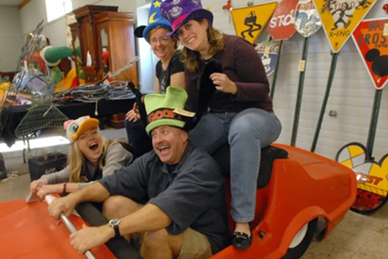Auction staffers pose for a photo wearing Disney hats and sitting in a car. Front: Jessica Blevins and Frank Renner; back: Linda Gagliardi, left, and Alicia Barnett, right. (April Saul / Staff Photographer)