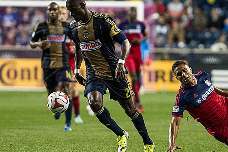 Fire forward Quincy Amarikwa slips while chasing Union midfielder Maurice Edu. (John Geliebter/USA Today Sports)