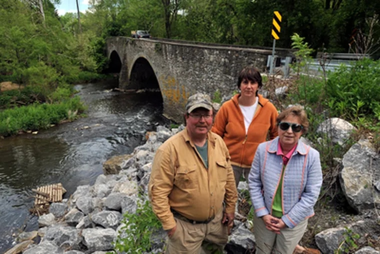 Rick Rasmussen (left to right), owner of Brandywine Outfitters and of the dam that crosses the Brandywine at Mortonville, Dee Durham, Executive Director of S.A.V.E, and Paula Coyne, Chairman of the East Fallowfield Historical Commission (and a board member of S.A.V.E.) stand in front of the Mortonville bridge over the Brandywine Creek.