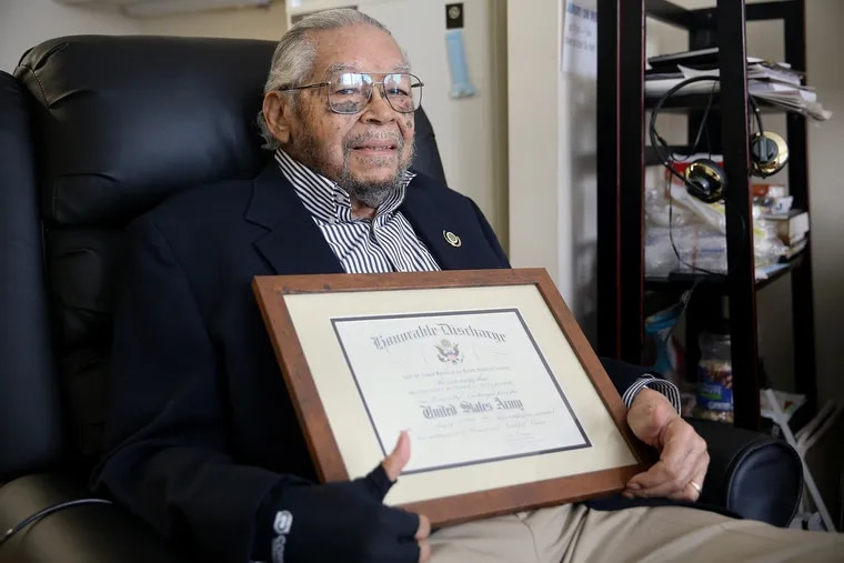 """Nelson Henry, 96, sits for a portrait with his U.S. Army honorable discharge certificate in his Logan Square apartment in Philadelphia on Thursday, Sept. 5, 2019. Henry was given a discriminatory """"blue discharge"""" in 1945, which was finally upgraded to honorable by Army Board for Correction of Military Records this year."""