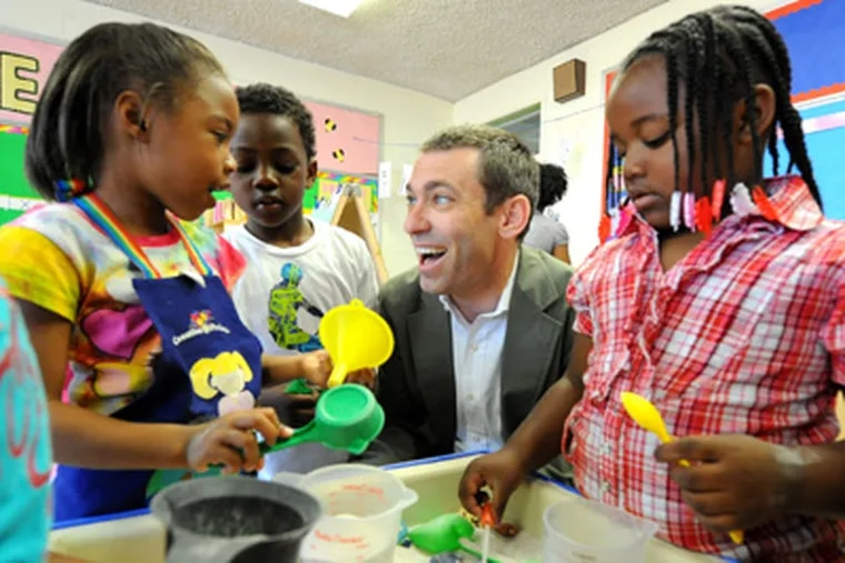 Aaron Lieberman in a classroom at Head Start center at St. Elizabeth's in North Philadelphia. Helping Lieberman are (from left) Amia Parker, Nyhka'r Butler and Saleeman Thompson. (Clem Murray / Staff Photographer)