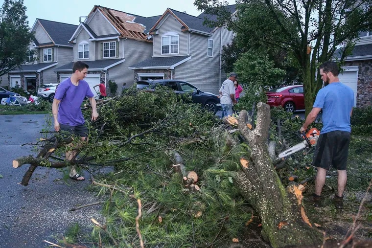 Homeowners and family members help clear trees after a possible tornado hit a small neighborhood in Morgantown, Pa., about 6 p.m. Tuesday, May 28, 2019