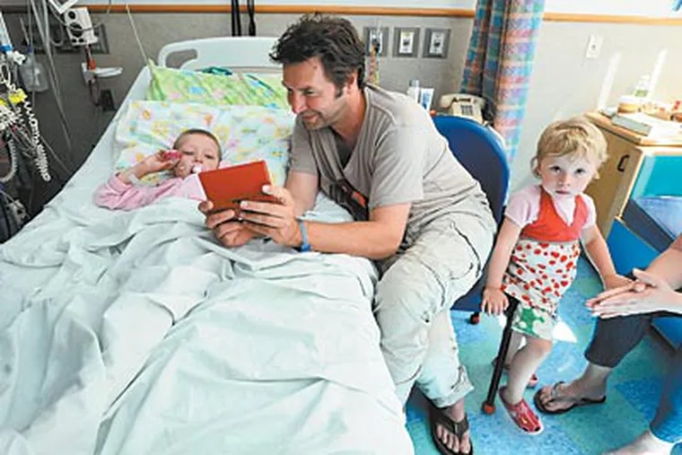Cancer patient Lise De Boer, 5, with father Alex and sister Famke at Children's Hospital. At the Colket building, doctors are working on new forms of treatment. (Bob Williams / For The Inquirer)