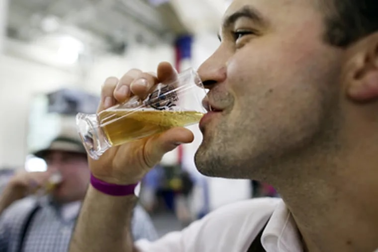 Jason Suda, from Philadelphia, tips his glass at the International Great Beer Expo at the Navy Yard in Philadelphia on Saturday. (Laurence Kesterson / Staff Photographer)
